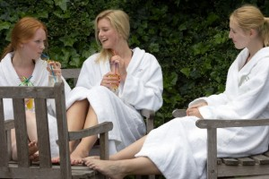 three female friends in white bathrobes drinking and chatting in the garden of a spa health club