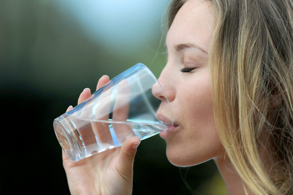 Closeup woman drinking water from glass