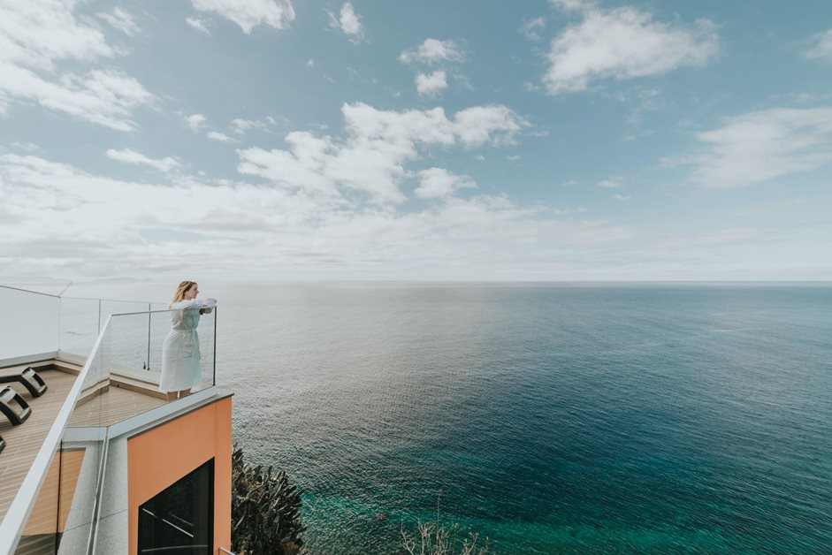 Woman looking out to sea on the balcony of a hotel in Madeira sunny