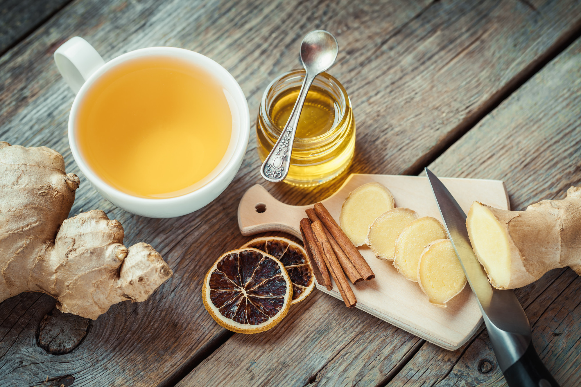 Ginger on cutting board, jar of honey, tea cup on kitchen table. Top view. spadreams kapha