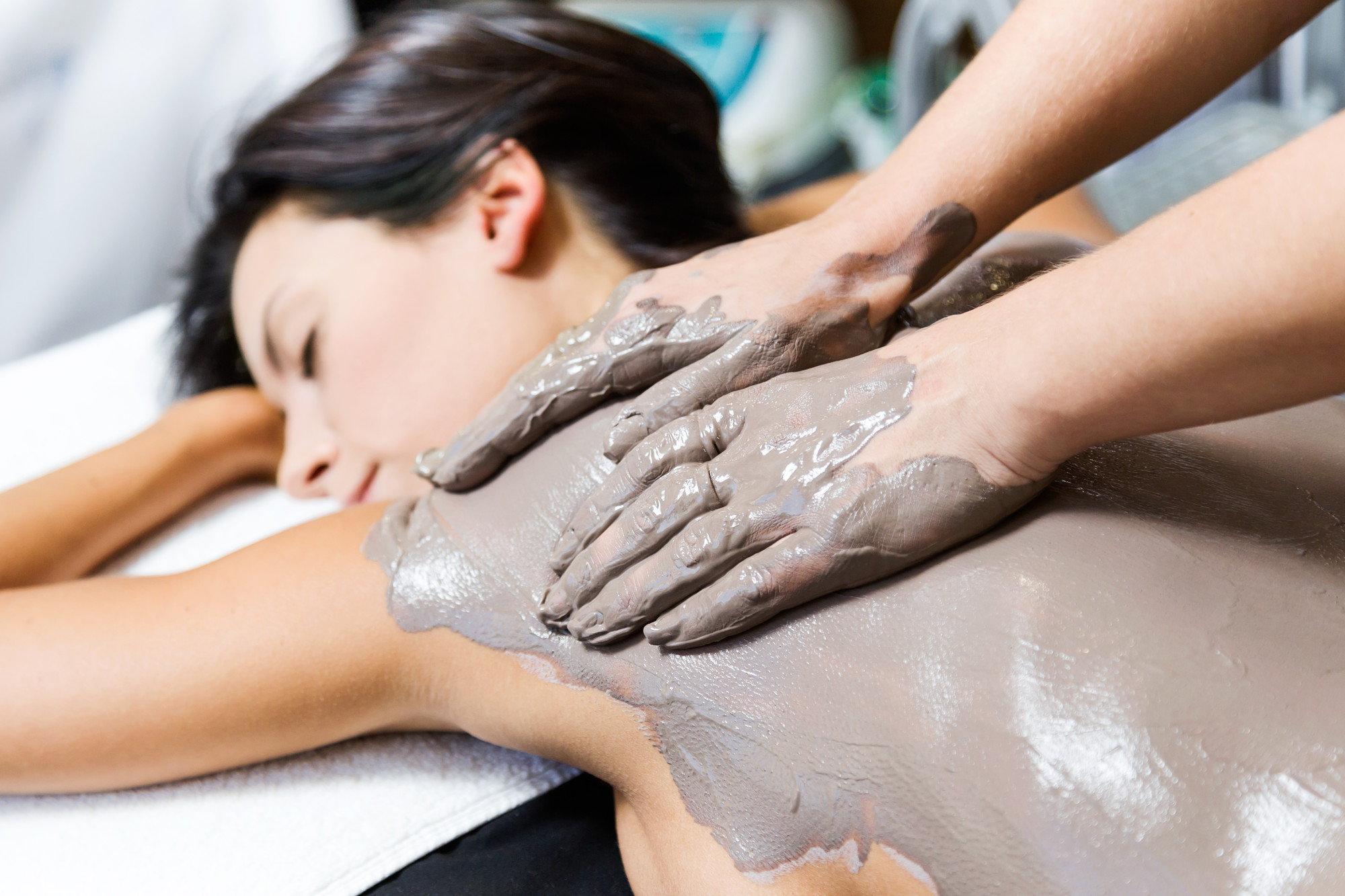 Portrait of beautiful young woman having clay body mask apply by beautician. Detox ritual. Mineral mud bathing with SpaDreams