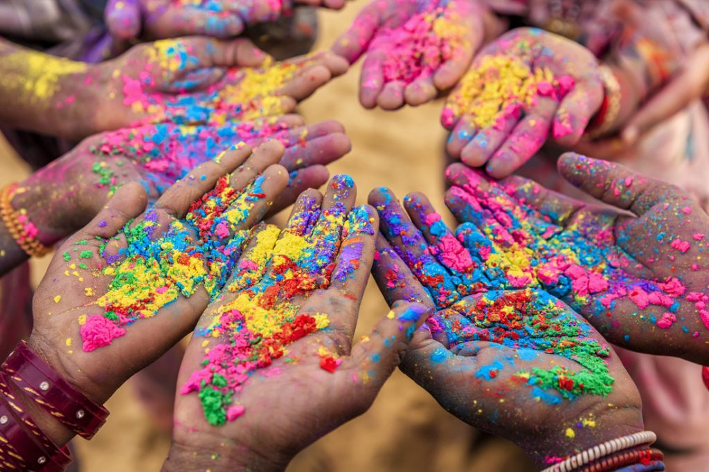 Group of Indian children playing happy holi in Rajasthan, India. Indian children keeping their hands up and showing colorful powders. Holi, the festival of colors, is a religious festival in India, celebrated, with the color powders, during the spring.