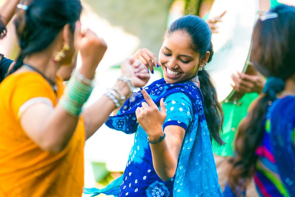 Young indian woman dancing with friends at holi