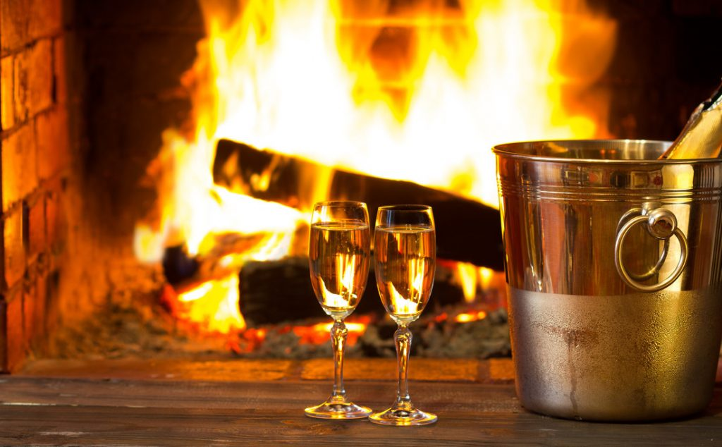 Two glasses of sparkling white wine in front of warm fireplace. Part of a pamper session for an evening of indoor activities.