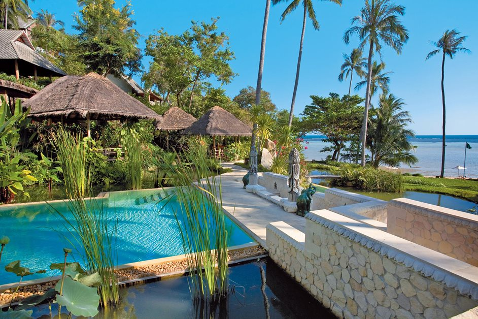 Beautiful outdoor pool next to sea with palm trees and beach huts in Indonesia
