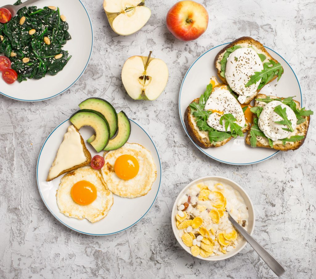 Helpful and tasty breakfast from different of dishes - fried egg, poached eggs, avocado, apple, spinach salad and muesli on light surface, top view
