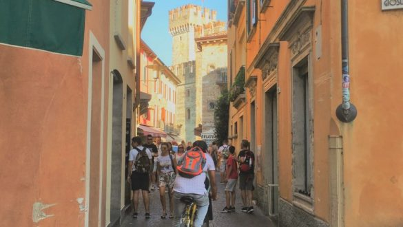 Man cycling through orange streets of sirmione.One of the best places to visit in Lake Garda. With SpaDreams