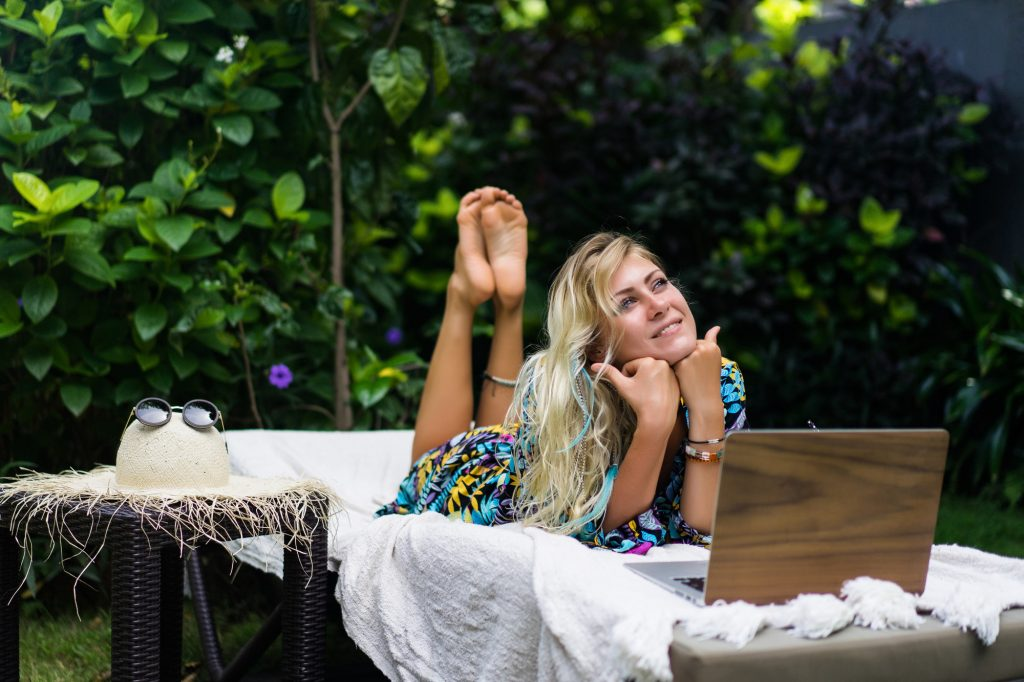 young woman dreaming and planning her next holiday with Covid19 travel tips