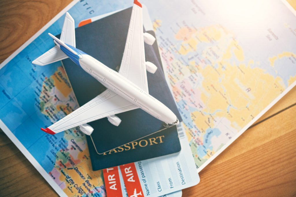 Model airplane, passports and airplane tickets on world map