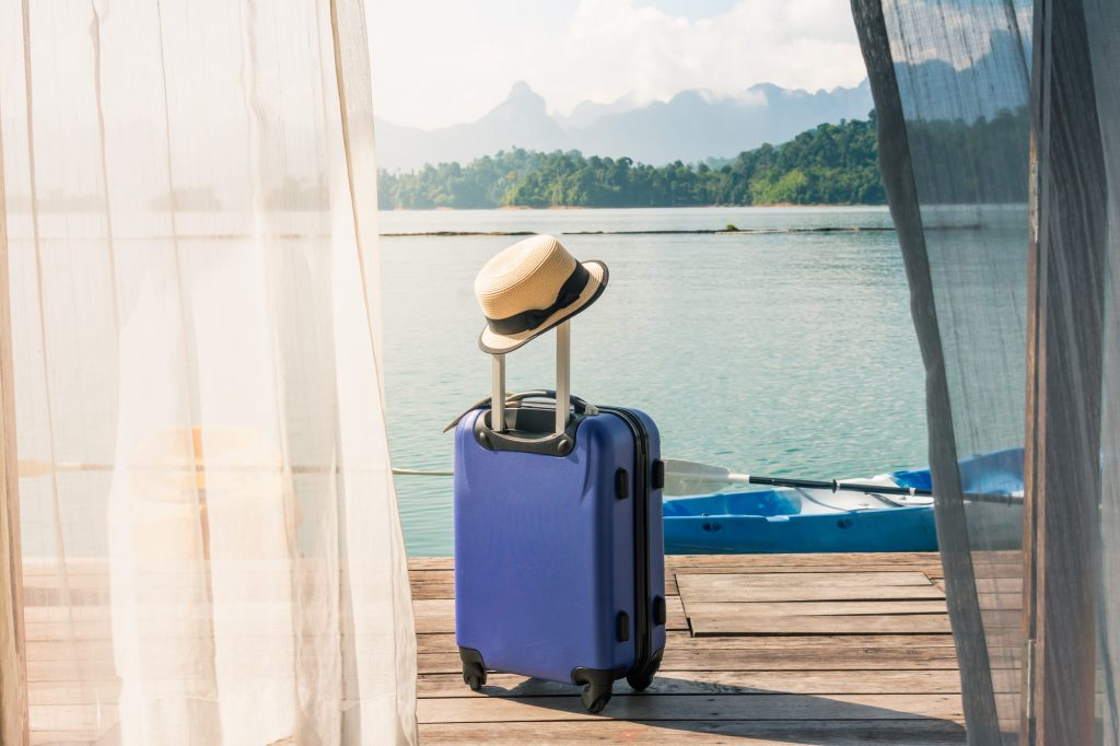 Suitcase on a terrace leading to a lake, a well planned trip with Covid19 travel tips.
