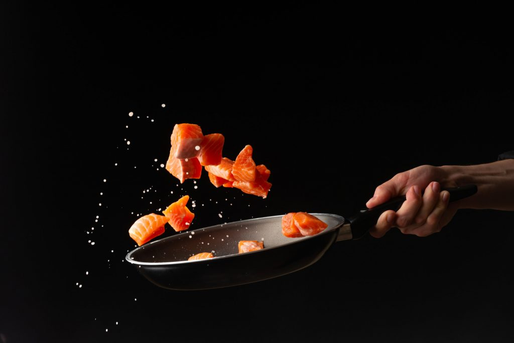 pieces of salmon being cast up from a frying pan