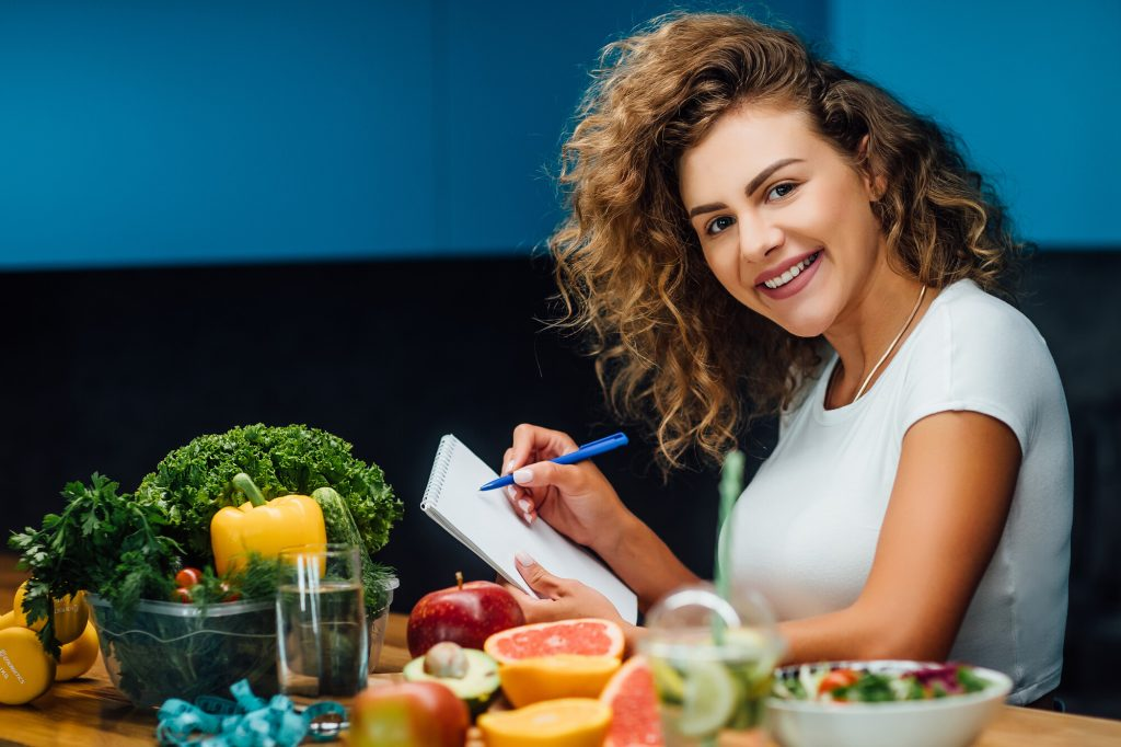 young woman sitting at a table filles with vegetables and fruits planning her pegan diet meals