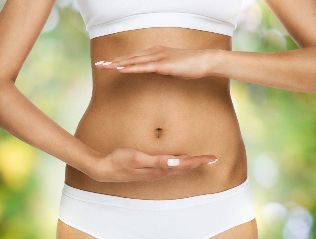 Woman holding her hands infront of her belly and around her navel - gut health