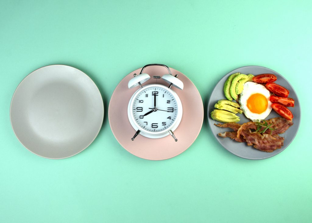 Intermittent fasting - three plates, one empty, one with a clock and one with a meal consisting of avocado, egg, tomatoes and bacon