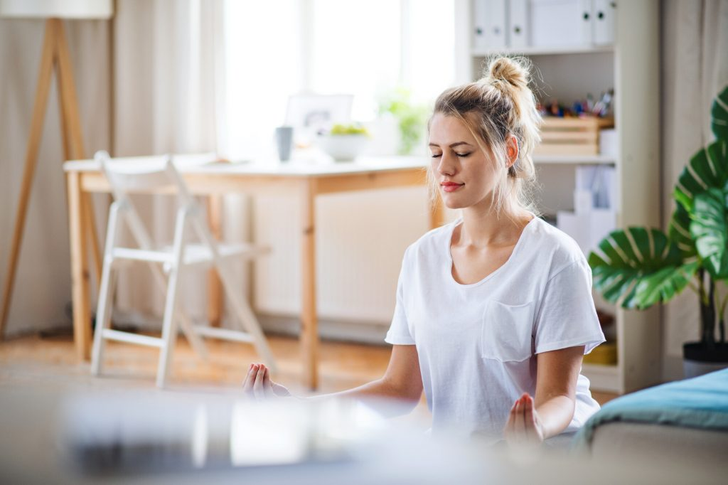 young woman practising yoga in her apartment - Ayurveda and yoga for weight loss