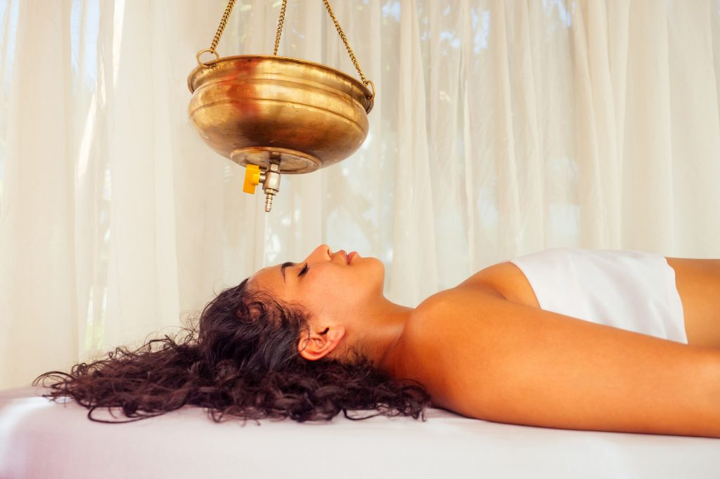 Young woman receiving a traditional Ayurveda treatment for migraines.