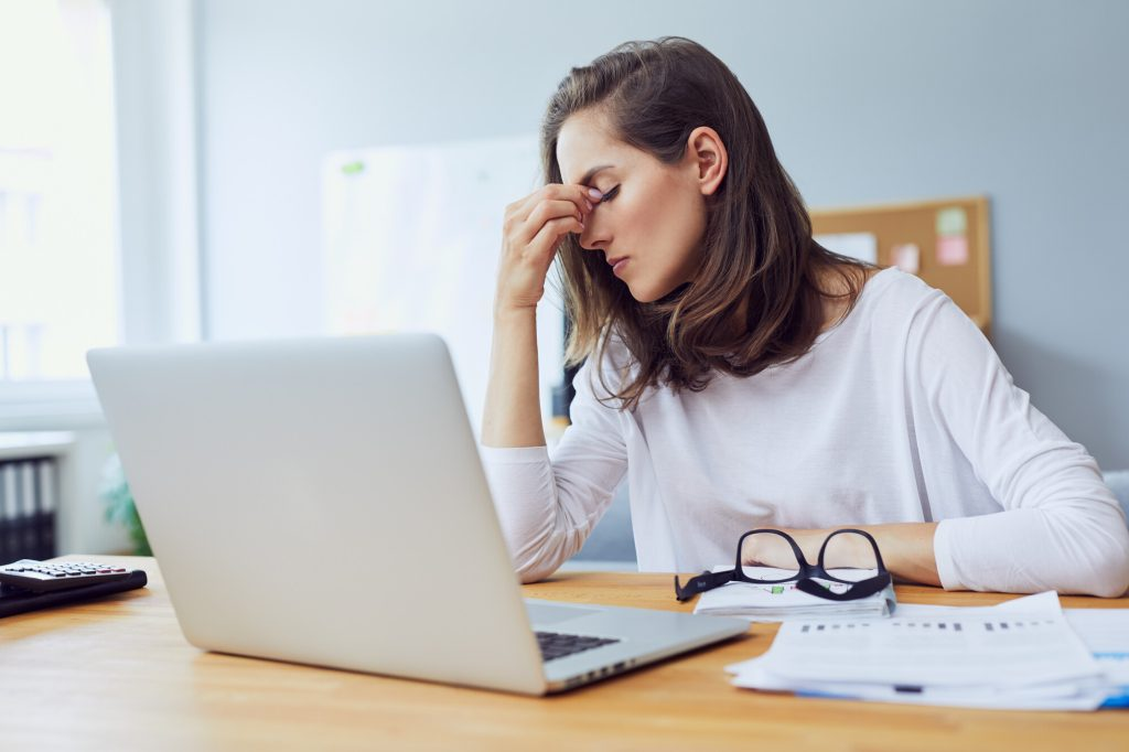 Young woman infront of a laptop looking stressed and holding her head in pain